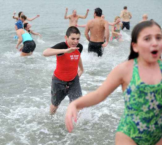 JD Rodia, age 14 center, runs out of the Long Island Sound at Compo Beach Tuesday morning Jan. 1, 2012, in Westport, Conn., during the Team Mossman Polar Plunge to benefit Save the Children. Photo: Lindsay Perry / Stamford Advocate
