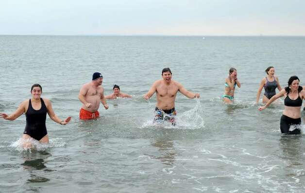 Adrian Mueller, center, celebrates after running into the Long Island Sound  Tuesday morning, Jan. 1, 2013, at Compo Beach in Westport, Conn., during the Team Mossman Polar Plunge to benefit Save the Children. Photo: Lindsay Perry / Stamford Advocate