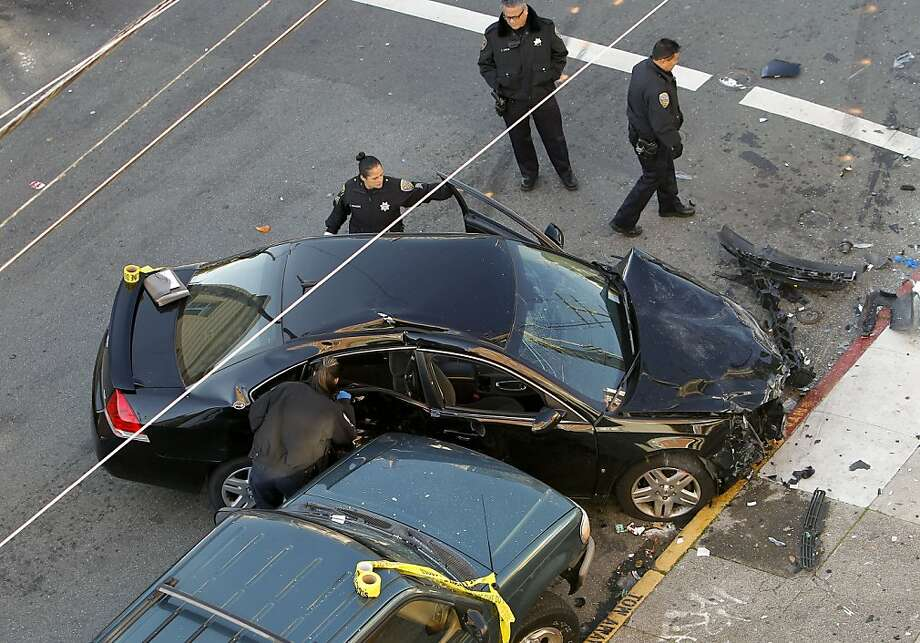 San Francisco police examine the suspect's black Chevrolet Impala near the corner of 21st Street and South Van Ness Avenue, where two people died. Photo: Michael Macor, The Chronicle
