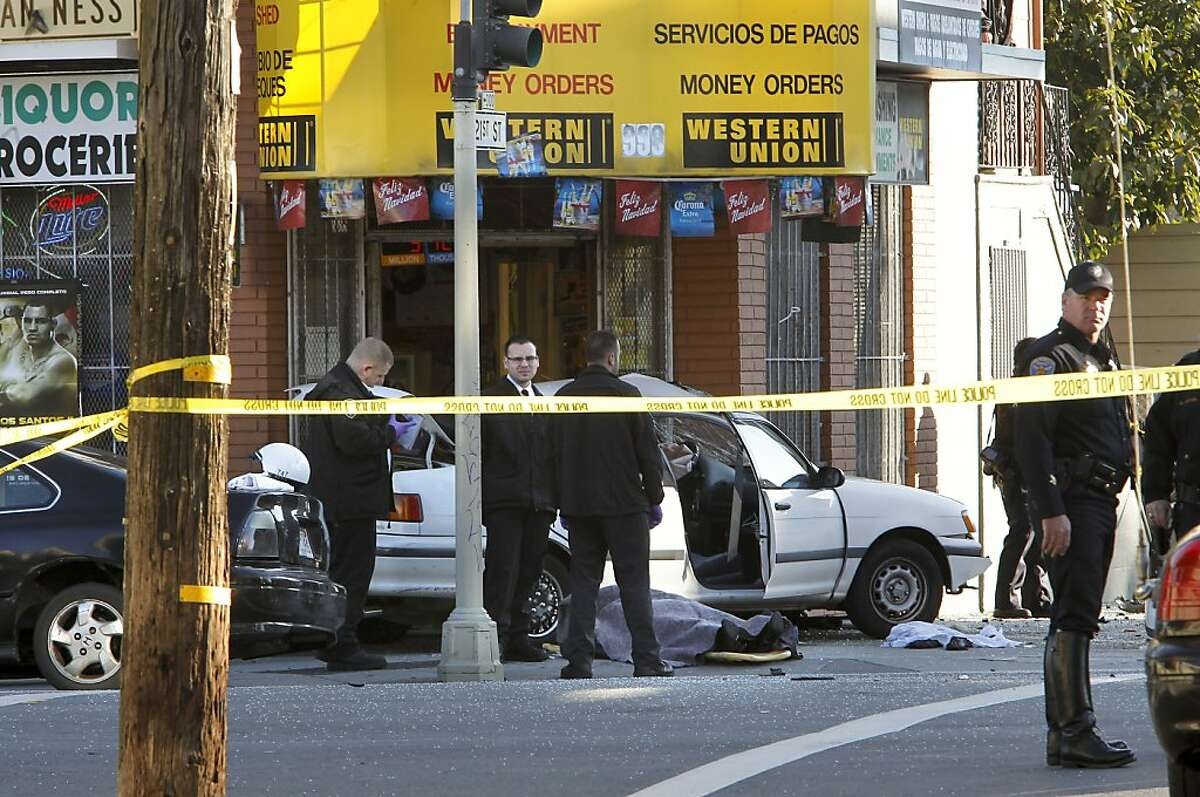 The body of one of the victims lies in front of a small liquor store as San Francisco police investigate the scene of a two car vehicle crash that left two people dead in San Francisco, Calif. at the corner of 21 St. and South Van Ness Ave. on Tuesday Jan. 1, 2013.