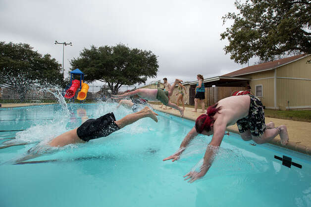 "FOR METRO - Henry Moses, right, dives into the pool during the 22nd Annual Polar Bear Swim for the Great Northwest Neighborhood Association at Silver Creek Pool on Tuesday, Jan. 1, 2013. This was Moses' fourth year participating, and when asked why he swims, he jokingly said ""Free T-shirt"". The first swim was January 1, 1991. MICHAEL MILLER / FOR THE EXPRESS-NEWS Photo: Michael Miller, For The Express-News  / San Antonio Express-News"