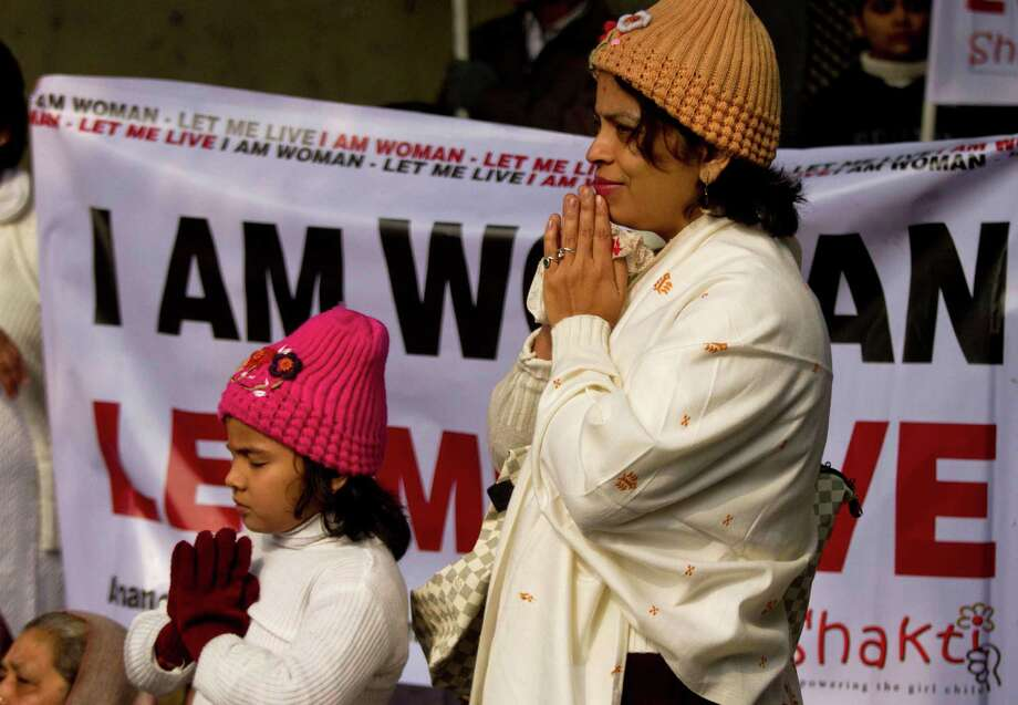 An Indian woman and her daughter pray as they take part in a silent protest to mourn the death of a gang rape victim in New Delhi, India, Tuesday, Jan. 1, 2013. The gang-rape and killing of a New Delhi student has set off an impassioned debate about what India needs to do to prevent such a tragedy from happening again. The country remained in mourning Tuesday, three days after the 23-year-old physiotherapy student died from her internal wounds in a Singapore hospital. (AP Photo/ Dar Yasin) Photo: Dar Yasin, Associated Press / AP
