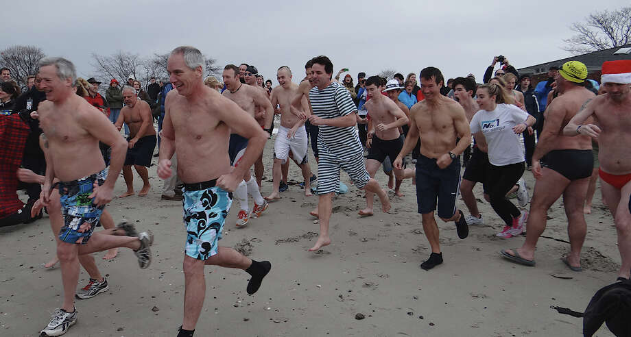 A crowd of brave swimmers heads into chilly Long Island Sound on Tuesday in the Team Mossman Triathlon Club's Polar Plunge Tuesday Jan. 1, 2013, at Compo Beach in Westport Conn. Photo: Mike Lauterborn / Westport News contributed