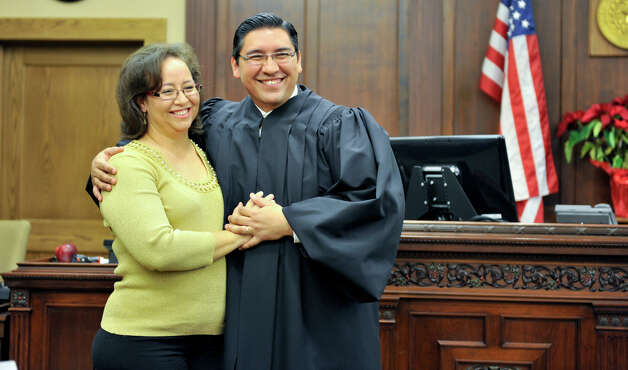 Newly elected 73rd Judicial District Court Judge David Canales smiles and hugs his wife Cecilia following his swearing-in Tuesday. Photo: Robin Jerstad