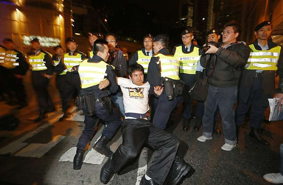 Police officers remove a man protesting the government as he blocks a road in downtown Hong Kong, after his group was prevented from marching on the chief executive's residence. Photo: Vincent Yu, Associated Press