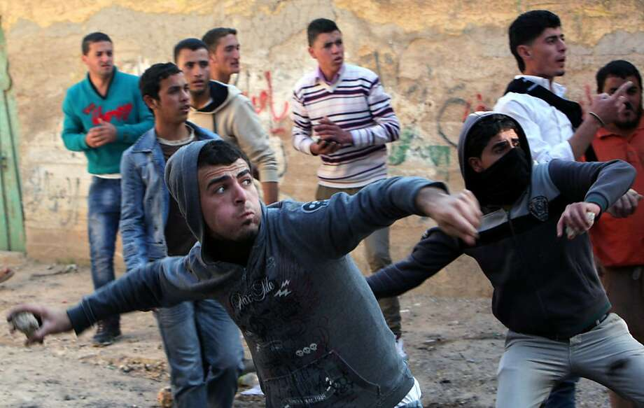 Palestinians hurl stones at Israeli soldiers (not pictured) in the West Bank village of Tamoun after an incursion by soldiers to arrest a wanted militant. Photo: Mohammed Ballas, Associated Press