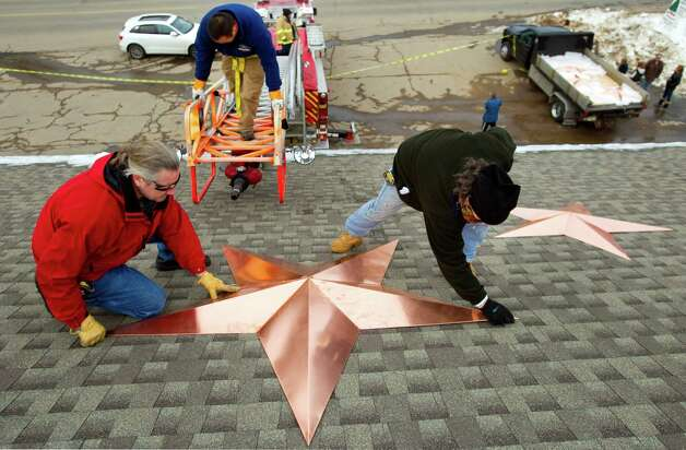 Greg Gnandt, left, and Guy Veneruso work on the installation of 26 stars on the roof of the Sandy Hook fire station Tuesday, Jan. 1, 2013, in Newtown, Conn. The stars were made and installed by a group of local contractors, led by Gnandt, to honor the memory of the victims of the Sandy Hook school shooting. Photo: Brett Coomer, Brett Coomer/Hearst Newspapers / The News-Times
