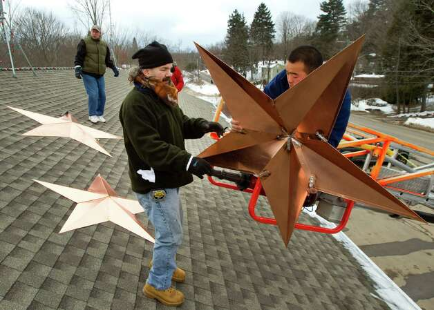 Guy Veneruso, left, takes a star from Matthew Hurley as they work on the installation of 26 stars on the roof of the Sandy Hook fire station Tuesday, Jan. 1, 2013, in Newtown, Conn. The stars were made and installed by a group of local contractors, led by Gnandt, to honor the memory of the victims of the Sandy Hook school shooting. Photo: Brett Coomer, Brett Coomer/Hearst Newspapers / The News-Times