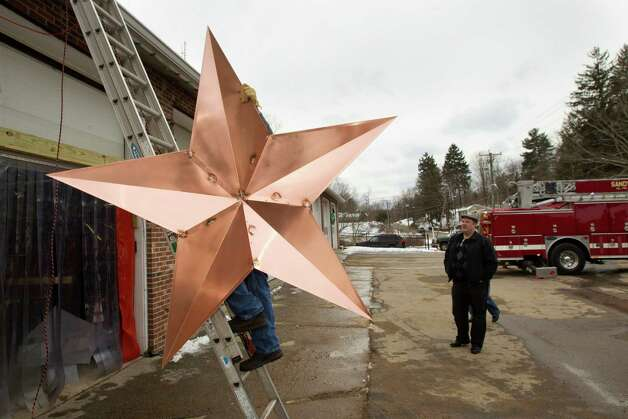 Greg Gnandt, left, carries a star to the roof of the Sandy Hook fire house as he and his crew install 26 stars on the roof of the Sandy Hook fire station Tuesday, Jan. 1, 2013, in Newtown, Conn. The stars were made and installed by a group of local contractors, led by Gnandt, to honor the memory of the victims of the Sandy Hook school shooting. Photo: Brett Coomer, Brett Coomer/Hearst Newspapers / The News-Times