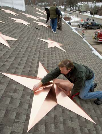 Craig Schultz places a star onto the roof of the Sandy Hook fire house as he helps with the installation of 26 stars at the station Tuesday, Jan. 1, 2013, in Newtown, Conn. The stars were made and installed by a group of local contractors, led by Greg Gnandt, to honor the memory of the victims of the Sandy Hook school shooting. Photo: Brett Coomer, Brett Coomer/Hearst Newspapers / The News-Times