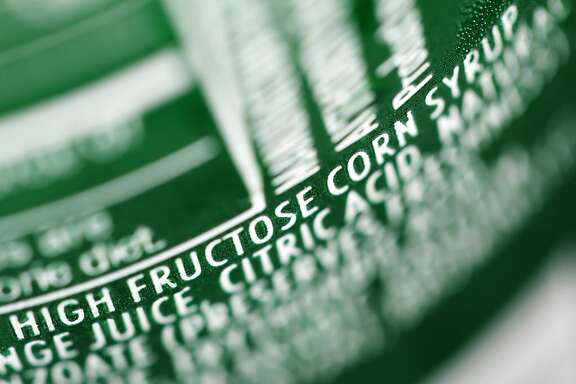 In this Sept. 15, 2011, file photo, high fructose corn syrup is listed as an ingredient on a can of soda in Philadelphia. Scientists have used imaging tests to show for the first time that fructose, a sugar that saturates the American diet, can trigger brain changes that may lead to overeating. The study, in the Journal of the American Medical Association on Tuesday, Jan. 1, 2013, is a small study and does not prove that fructose or its relative, high-fructose corn syrup, can cause obesity, but experts say it adds evidence they may play a role.