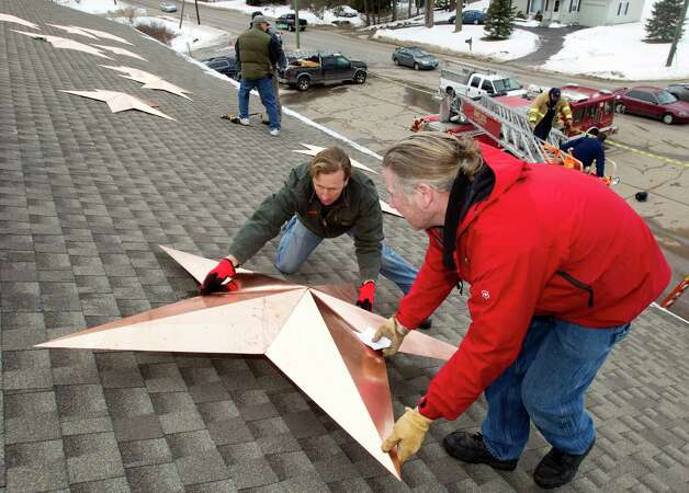 Craig Schultz, left, and Greg Gnandt place a star onto the roof of the Sandy Hook fire house as they install of 26 stars at the station Tuesday, Jan. 1, 2013, in Newtown, Conn. The stars were made and installed by a group of local contractors, led by Greg Gnandt, to honor the memory of the victims of the Sandy Hook school shooting. Photo: Brett Coomer, Brett Coomer/Hearst Newspapers / The News-Times