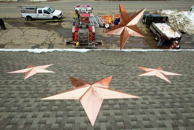 Matthew Hurley holds onto a copper star as he helps with the installation of 26 stars on the roof of the Sandy Hook fire station Tuesday, Jan. 1, 2013, in Newtown, Conn. The stars were made and installed by a group of local contractors, led by Greg Gnandt, to honor the memory of the victims of the Sandy Hook school shooting. Photo: Brett Coomer, Brett Coomer/Hearst Newspapers / The News-Times
