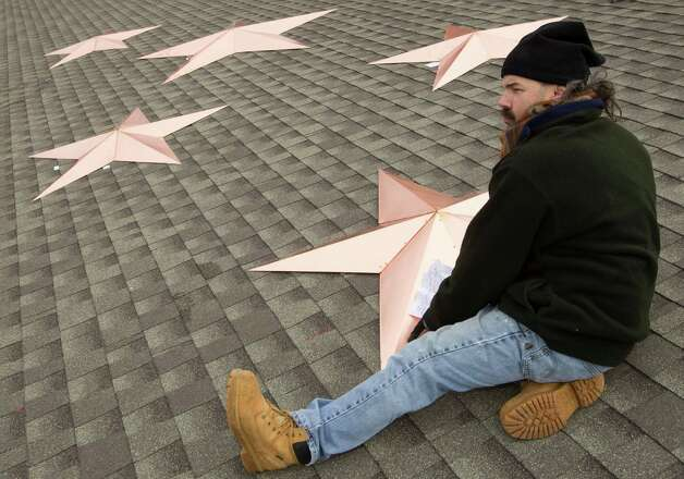 Guy Veneruso places a star onto the roof of the Sandy Hook fire house as he helps with the installation of 26 stars at the station Tuesday, Jan. 1, 2013, in Newtown, Conn. The stars were made and installed by a group of local contractors, led by Greg Gnandt, to honor the memory of the victims of the Sandy Hook school shooting. Photo: Brett Coomer, Brett Coomer/Hearst Newspapers / The News-Times