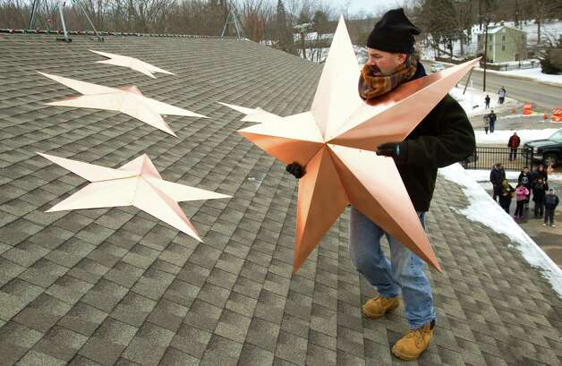 Guy Veneruso preares to place a star onto the roof of the Sandy Hook fire house as he helps with the installation of 26 stars at the station Tuesday, Jan. 1, 2013, in Newtown, Conn. The stars were made and installed by a group of local contractors, led by Greg Gnandt, to honor the memory of the victims of the Sandy Hook school shooting. Photo: Brett Coomer, Brett Coomer/Hearst Newspapers / The News-Times