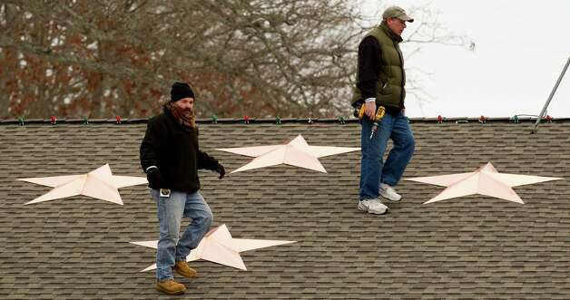 Guy Veneruso, left, and Len Sabia walk on the roof of the Sandy Hook fire station as they work on the installation of 26 stars to the station Tuesday, Jan. 1, 2013, in Newtown, Conn. The stars were made and installed by a group of local contractors, led by Greg Gnandt, in memory of the victims of the Sandy Hook school shooting. Photo: Brett Coomer, Brett Coomer/Hearst Newspapers / The News-Times