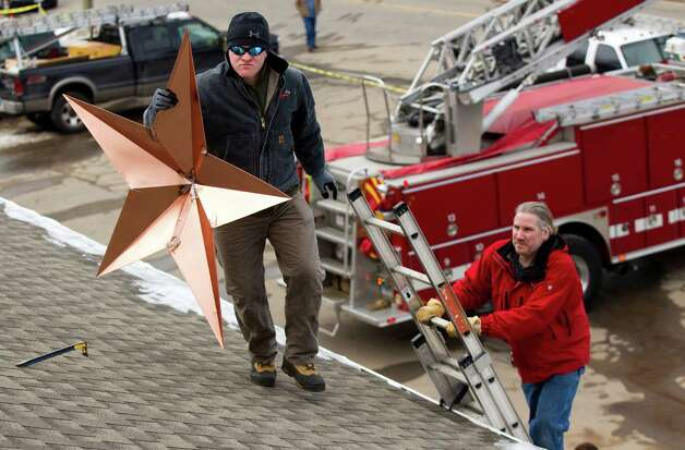 Adrian Szepietowski carries a star to the roof of the Sandy Hook fire station while helping with the installation of 26 stars to the station Tuesday, Jan. 1, 2013, in Newtown, Conn. The stars were made and installed by a group of local contractors, led by Greg Gnandt, on ladder, in memory of the victims of the Sandy Hook school shooting. Photo: Brett Coomer, Brett Coomer/Hearst Newspapers / The News-Times