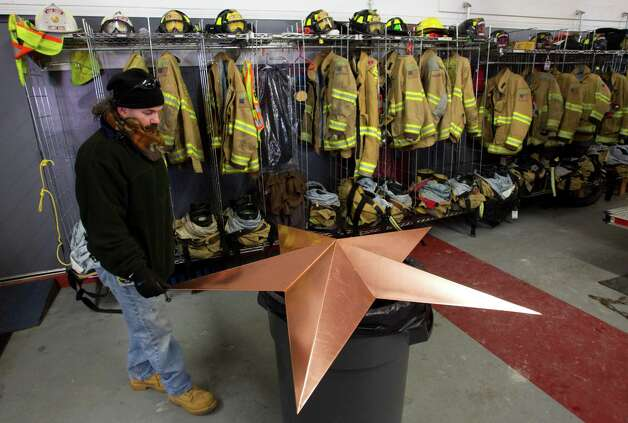 Guy Veneruso places a star inside the Sandy Hook fire station while preparing to help with the installation of 26 stars to the station's roof Tuesday, Jan. 1, 2013, in Newtown, Conn. The stars were made and installed by a group of local contractors, led by Greg Gnandt, in memory of the victims of the Sandy Hook school shooting. Photo: Brett Coomer, Brett Coomer/Hearst Newspapers / The News-Times