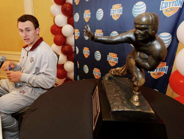 Texas A&M freshman quarterback Johnny Manziel answer questions during a Cotton Bowl press conference, with a Heisman Trophy at side, at the Omni Mandalay hotel, Tuesday, Jan. 1, 2013, in Irving, Texas. Texas A&M plays Oklahoma on Jan. 4 in the Cotton Bowl in Arlington, Texas. Photo: Brandon Wade, Associated Press / FR168019 AP