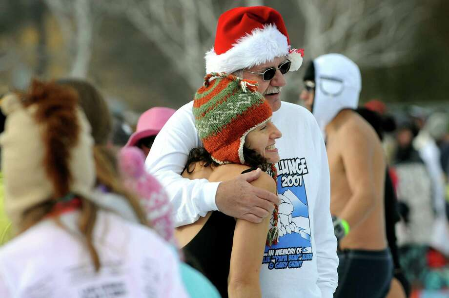 Traci Peters of Troy, center, poses with her father, Al Smith of Warrensburg, before taking the annual Polar Bear Plunge on Tuesday, Jan. 1, 2013, at Million Dollar Beach in Lake George, N.Y. (Cindy Schultz / Times Union) Photo: Cindy Schultz / 00020600A