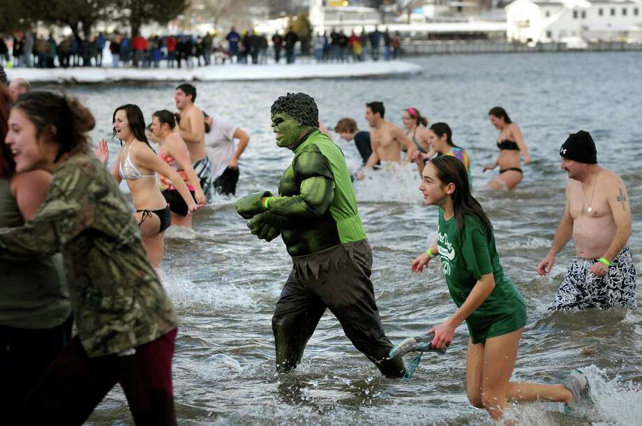 Participants, including the Incredible Hulk, center, take the annual Polar Bear Plunge on Tuesday, Jan. 1, 2013, at Million Dollar Beach in Lake George, N.Y. (Cindy Schultz / Times Union) Photo: Cindy Schultz / 00020600A