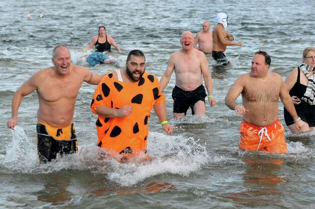 Tony Dandreti of Rotterdam, center, dressed as Fred Flintstone, joins friends in the annual Polar Bear Plunge on Tuesday, Jan. 1, 2013, at Million Dollar Beach in Lake George, N.Y. (Cindy Schultz / Times Union) Photo: Cindy Schultz / 00020600A