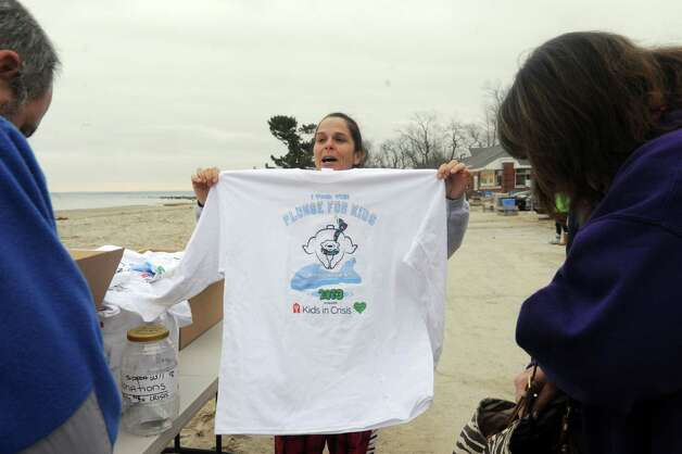"Angela Swift, of Riverside, selling Plunge for Kids T-shirt before the first annual ""I Took the Plunge for Kids"" polar plunge to benefit Kids in Crisis, to run, jump or dunk their heads under the freezing water at Tod's Point in Old Greenwich, Conn., Tuesday, Jan. 1, 2013. All proceeds from the event will go to Kids in Crisis. Photo: Helen Neafsey / Greenwich Time"