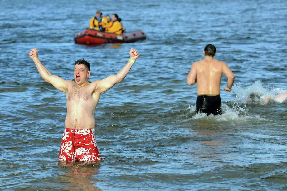 A participant celebrates in the freezing water during the annual Polar Bear Plunge on Tuesday, Jan. 1, 2013, at Million Dollar Beach in Lake George, N.Y. (Cindy Schultz / Times Union) Photo: Cindy Schultz / 00020600A
