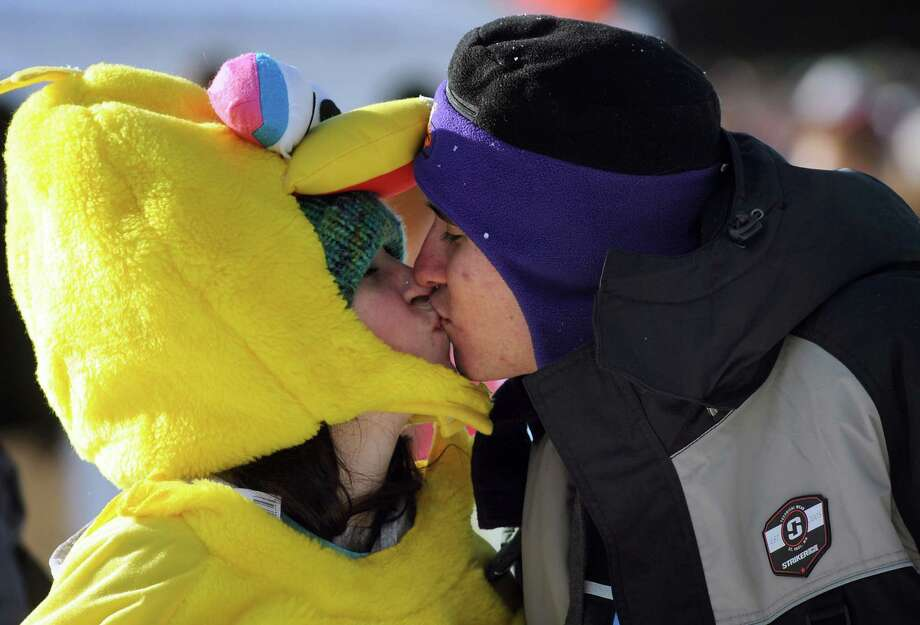 Mikayla Rivers, dressed as Big Bird, left, and Stephen Mann, both of Glens Falls, share a kiss after taking the annual Polar Bear Plunge on Tuesday, Jan. 1, 2013, at Million Dollar Beach in Lake George, N.Y. (Cindy Schultz / Times Union) Photo: Cindy Schultz / 00020600A