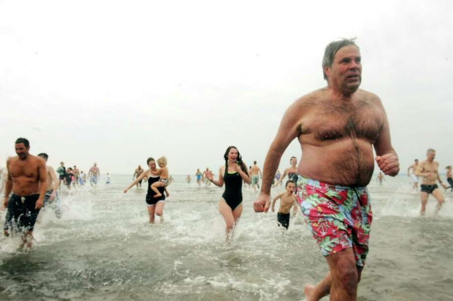 "A man comes out of the water at the first annual ""I Took the Plunge for Kids"" polar plunge to benefit Kids in Crisis, to run, jump or dunk their heads under the freezing water at Tod's Point in Old Greenwich, Conn., Tuesday, Jan. 1, 2013. All proceeds from the event will go to Kids in Crisis. Photo: Helen Neafsey / Greenwich Time"