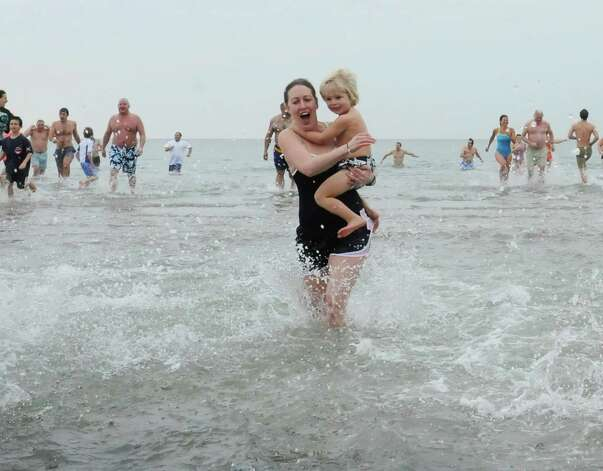"A woman carries her son at the first annual ""I Took the Plunge for Kids"" polar plunge to benefit Kids in Crisis, to run, jump or dunk their heads under the freezing water at Tod's Point in Old Greenwich, Conn., Tuesday, Jan. 1, 2013. All proceeds from the event will go to Kids in Crisis. Photo: Helen Neafsey / Greenwich Time"