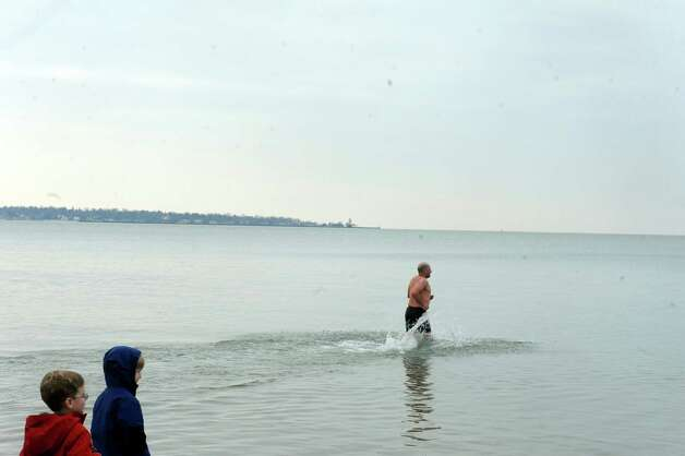 "A man took one more plunge at the first annual ""I Took the Plunge for Kids"" polar plunge to benefit Kids in Crisis, to run, jump or dunk their heads under the freezing water at Tod's Point in Old Greenwich, Conn., Tuesday, Jan. 1, 2013. All proceeds from the event will go to Kids in Crisis. Photo: Helen Neafsey / Greenwich Time"