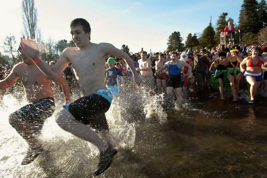 Revelers race into the chilly water of Lake Washington.