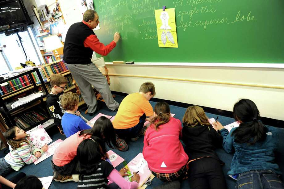 Teacher Lester Betor, left, writes in cursive on the chalkboard for this fifth-grade class on Wednesday, Dec. 19, 2012, at Slingerlands Elementary in Bethlehem, N.Y. (Cindy Schultz / Times Union) Photo: Cindy Schultz / 00020507A