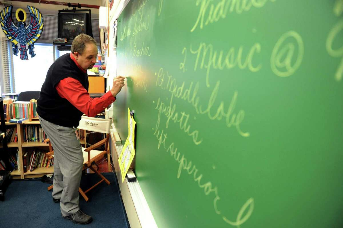Teacher Lester Betor, left, writes in cursive on the chalkboard for this fifth-grade class on Wednesday, Dec. 19, 2012, at Slingerlands Elementary in Bethlehem, N.Y. (Cindy Schultz / Times Union)