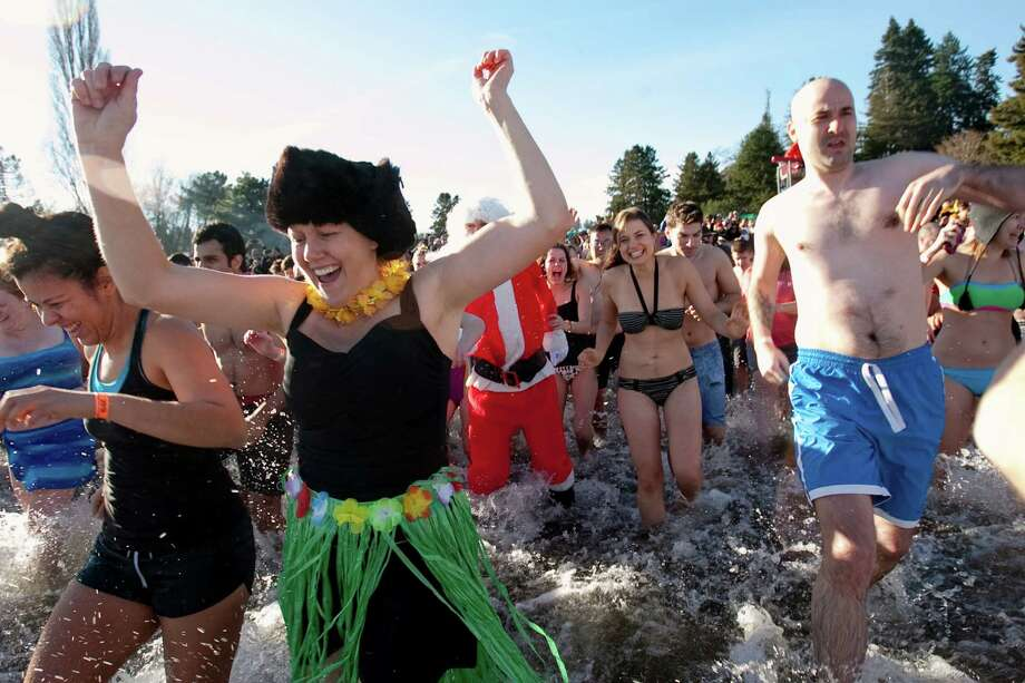 Michelle Gherardi, left, races into the chilly water of Lake Washington during the 11th annual Polar Bear Plunge at Matthews Beach. Photo: JOSHUA TRUJILLO / SEATTLEPI.COM
