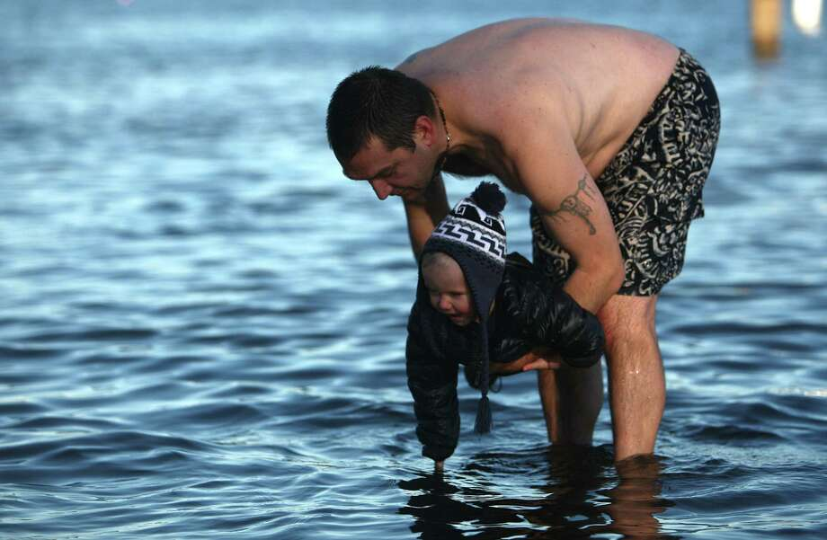 A young participant touches the chilly water of Lake Washington. Photo: JOSHUA TRUJILLO / SEATTLEPI.COM