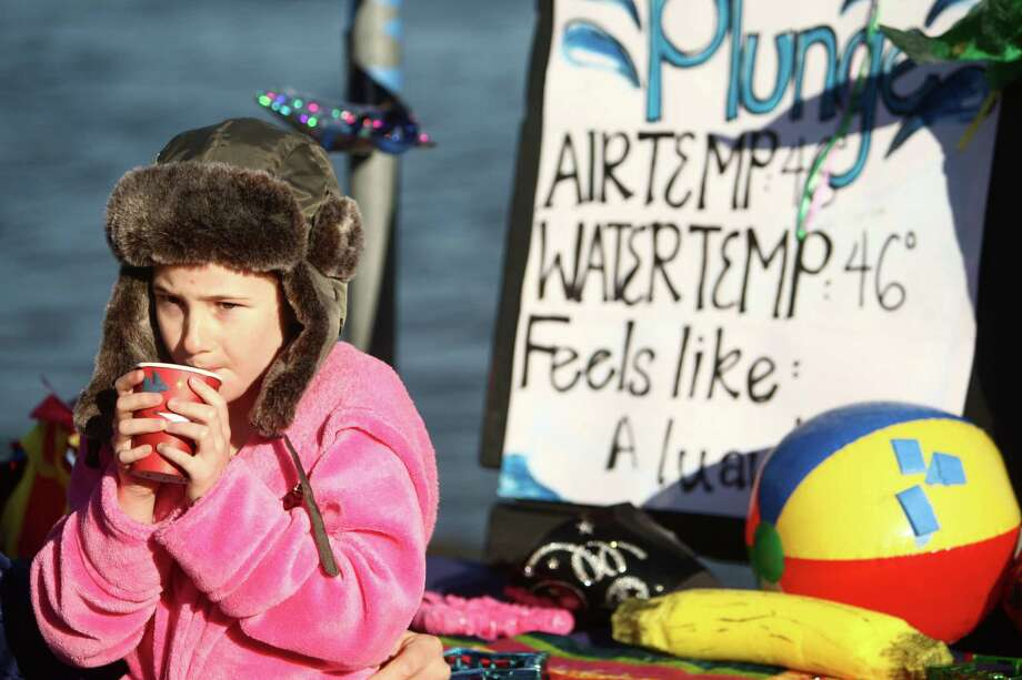 A participant warms up after taking a dip in the chilly water of Lake Washington during the 11th annual Polar Bear Plunge at Matthews Beach on Tuesday, January 1, 2013. The annual event celebrates the beginning of a new year. Photo: JOSHUA TRUJILLO / SEATTLEPI.COM