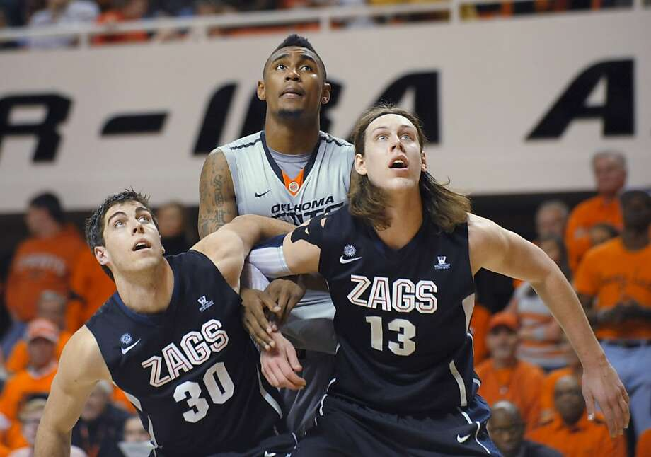 Gonzaga guard Michael Hart, left, and forward Kelly Olynyk, right, block out Oklahoma State guard Le'Bryan Nash during the second half of an NCAA college basketball game in Stillwater, Okla., Monday, Dec. 31, 2012. Olynyk scored 21 points as Gonzaga won 69-68. (AP Photo/Brody Schmidt) Photo: Brody Schmidt, Associated Press
