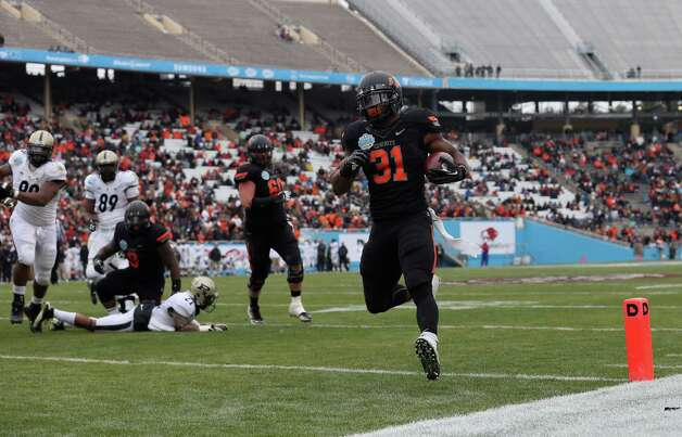 Heart of Dallas Bowl, Jan. 1: Oklahoma State 58, Purdue 14; Cotton Bowl in Dallas; Payout: $1,100,000 PHOTO: Oklahoma State's Jeremy Smith runs for a touchdown against Purdue during the Heart of Dallas Bowl. Photo: Ronald Martinez, Getty Images / 2013 Getty Images
