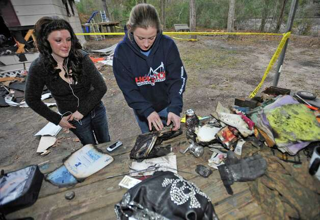 Stephanie Wales, right, and 13 year old daughter Kendra, left, try to salvage newly found picture albums. Stephanie and Burton Wales lost their home in a fire on December 21, 2012, that also seriously burned their teenage daughter and killed their three dogs who had woke them up. They live in Lumberton at 108 Hawn Street. Now two friends are working to help them rebuild the home because they did not have insurance. On Monday, they were at the home trying to salvage more of their belongings.  Dave Ryan/The Enterprise Photo: Dave Ryan