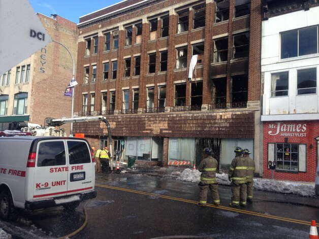 Firefighters survey the scene Dec. 28, 2012 after a fire at 237-247 State St., Schenectady, the day before gutted the apartment building and forced the city to temporarily close a stretch of the downtown street. (PAUL NELSON / TIMES UNION)