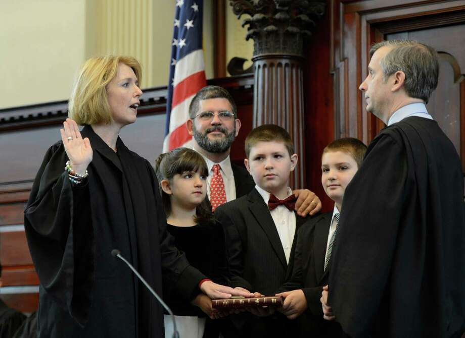 Rensselaer County Court Judge Debra Young, left  takes the Oath of Office from U.S. Magistrate Christian Hummel during the swearing in ceremony at the Rensselaer County Courthouse in Troy, N.Y.  Jan 1, 2013. With Young is her family husband Christopher, background, daughter Charlotte, 6; Samuel, 11 and Gabriel, 9.  (Skip Dickstein/Times Union) Photo: SKIP DICKSTEIN / 00020588A