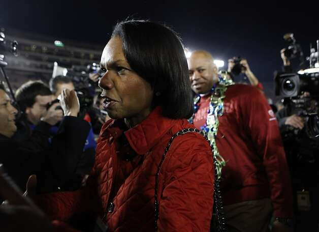 Stanford scholar Condoleezza Rice works her way through a crowd  of photographers after congratulating head coach David Shaw (background) on the Cardinal victory over Wisconsin at the Rose Bowl in Pasadena, Calif. on Tuesday, Jan. 1, 2013. Photo: Paul Chinn, The Chronicle