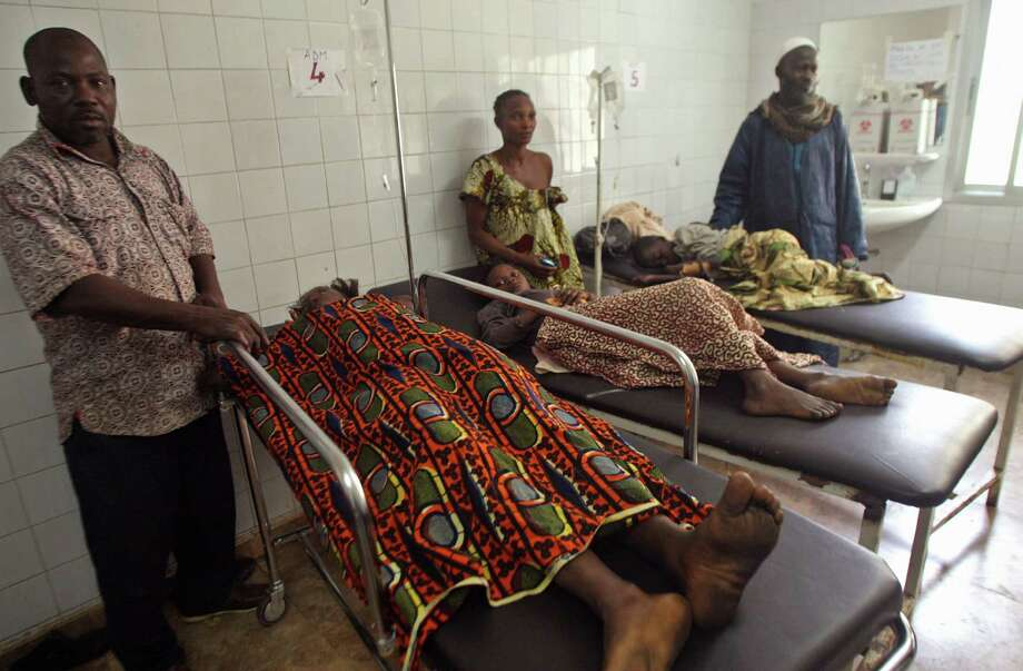 Injured people are seen at a hospital with their family members standing with them, after they were involved in a  stampeded in Abidjan, Ivory Coast, Tuesday, Jan. 1, 2013. At least 61 people were killed early Tuesday in a stampede following a New Year's fireworks display in Abidjan, Ivory Coast's commercial center, said officials. The death toll is expected to rise, according to rescue workers. The majority of those killed were young people between eight and 15 years old who were trampled after the fireworks festivities in Abidjan's Plateau district, at about 1 a.m. Tuesday, said Col. Issa Sako, of the fire department rescue team. (AP Photo/Emanuel Ekra) Photo: Emanuel Ekra