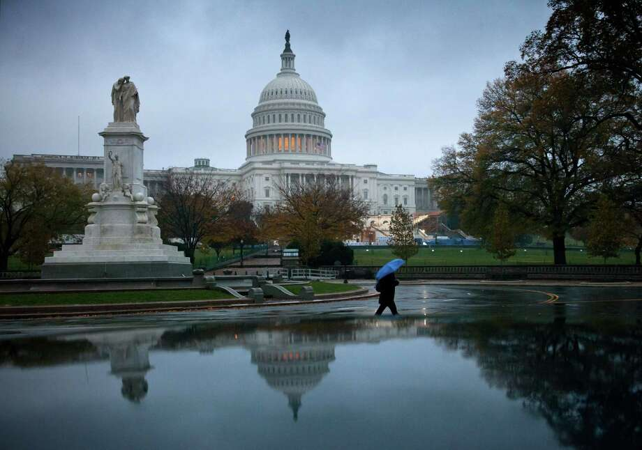 FILE - In this Nov. 13, 2012 file photo, a man walks in front of the Capitol in Washington. The debate in Washington over taxes and spending is likely to continue damaging the fragile economy well into 2013. The political standoff has already taken an economic toll, creating uncertainty about the future and discouraging consumers from spending and businesses from hiring and investing. (AP Photo/J. Scott Applewhite, File) Photo: J. Scott Applewhite