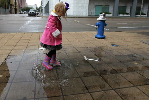 Sophia Oncken, 3,  plays in a puddle on San Jacinto Street, Tuesday, Jan. 1, 2013, in Houston. Oncken said that she likes her rain boots after getting them for Christmas. Photo: Cody Duty, Houston Chronicle / © 2012 Houston Chronicle