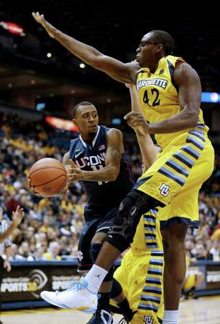 Connecticut's Ryan Boatright, left, passes around Marquette's Chris Otule(42) during the second of an NCAA college basketball game Tuesday, Jan. 1, 2013, in Milwaukee. (AP Photo/Jeffrey Phelps) Photo: Jeffrey Phelps, Associated Press / FR59249 AP