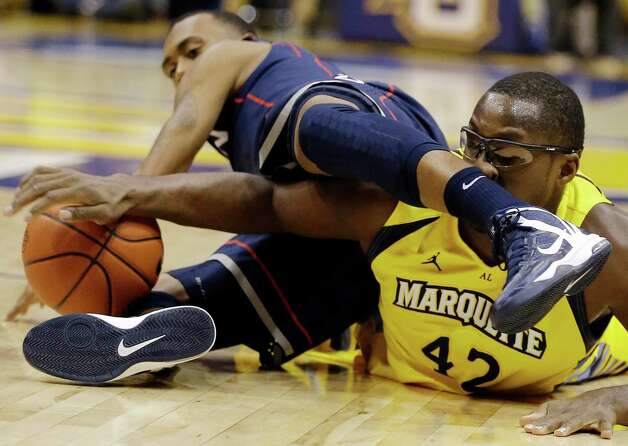 Marquette's Chris Otule (42) and Connecticut's Ryan Boatright, left, dive for a loose ball during the first half of an NCAA college basketball game, Tuesday, Jan. 1, 2013, in Milwaukee. (AP Photo/Jeffrey Phelps) Photo: JEFFREY PHELPS, Associated Press / FR59249 AP