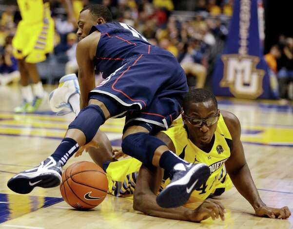 Marquette's Chris Otule, right, and Connecticut's Ryan Boatright (11) dive for a loose ball during the first half of an NCAA college basketball game, Tuesday, Jan. 1, 2013, in Milwaukee. (AP Photo/Jeffrey Phelps) Photo: JEFFREY PHELPS, Associated Press / FR59249 AP